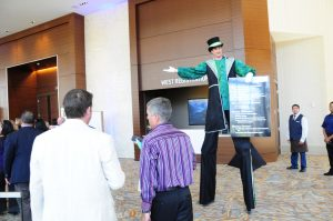 Tall man greets guests and press holding a menu of the complimentary eats.