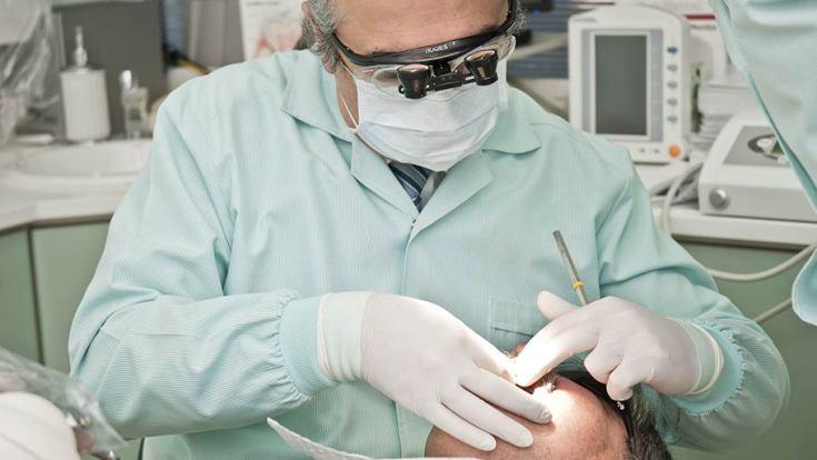 Photographie d'un dentiste réalisant une intervention sur un patient à la bouche ouverte. Cette photo illustre l'utilisation de l'hypnose et de l'hypnothérapie en milieu médical et thérapeutique.
