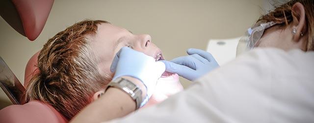 Peur du dentiste : photographie d'un enfant en train de se faire soigner les dents par une femme.