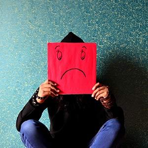 Anxiété et stress : un homme assis par terre contre un mur décoré d'un papier peint fleuri vieillot tient dans ses mains une pancarte rouge masquant son visage et affichant un smiley triste dessiné au feutre.