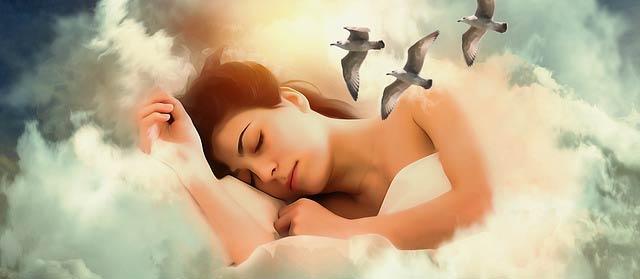 Femme endormie rapidement grâce à l'hypnose qui permet de dormir mieux. Allongée sur des nuages, la têtes entourée de mouettes, elle se laisse aller aux rêves.