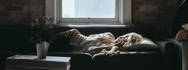 Femme endormie sur un canapé devant une fenêtre. L'hypnose et l'auto-hypnose peuvent permettre de dormir mieux et de s'endormir plus rapidement.