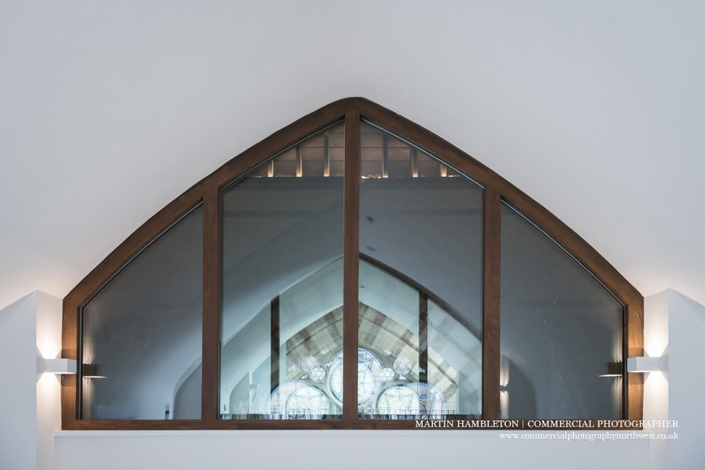 modern window reflecting church interior trinity development altrincham