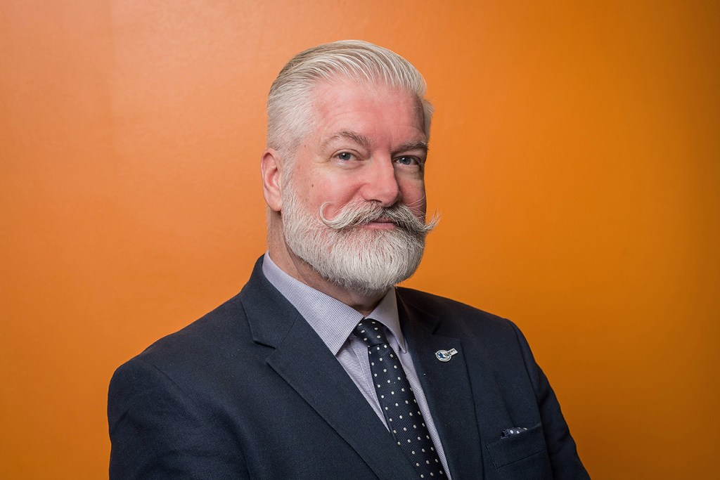 headshot photo of man in suit and tie against orange background