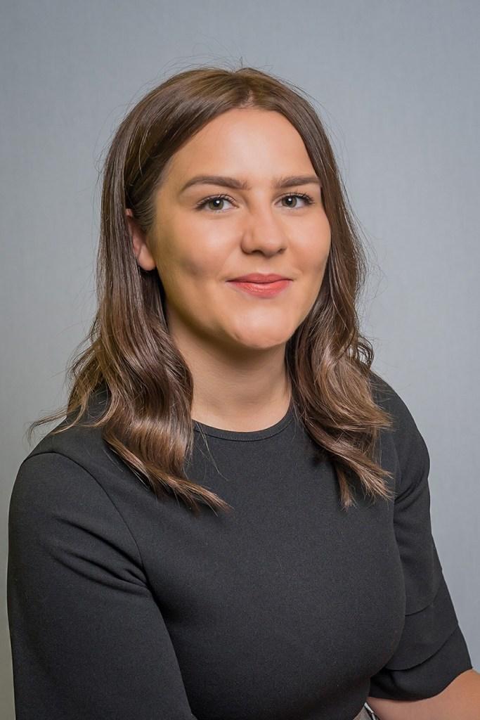 headshot photo of woman smiling at camera wearing dark top