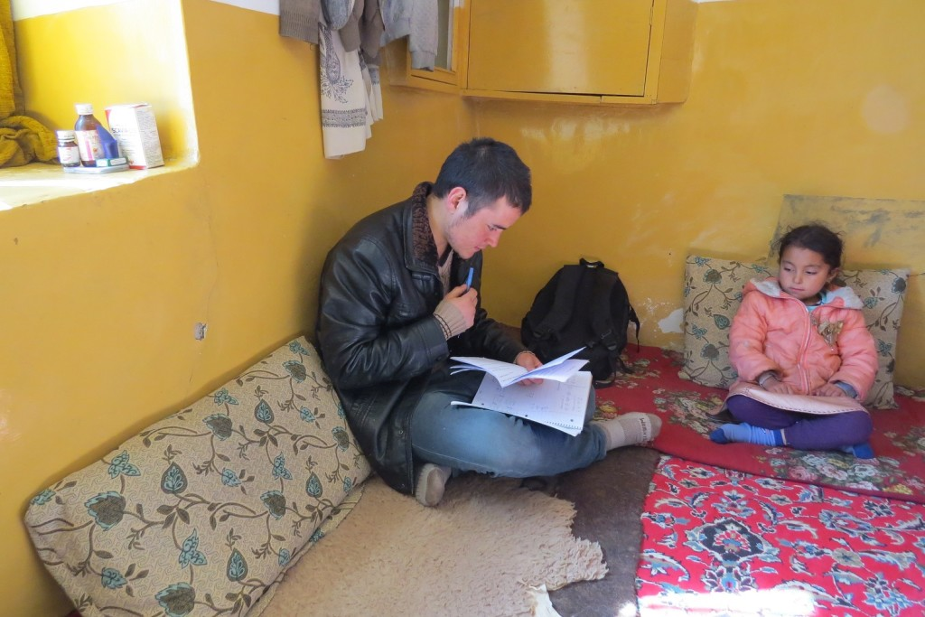 Zek conducting the survey in Zuhair's home. Zuhair's sister is looking on.
