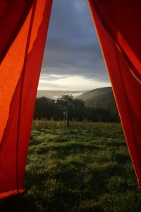 the view through a tent door at dawn across the field
