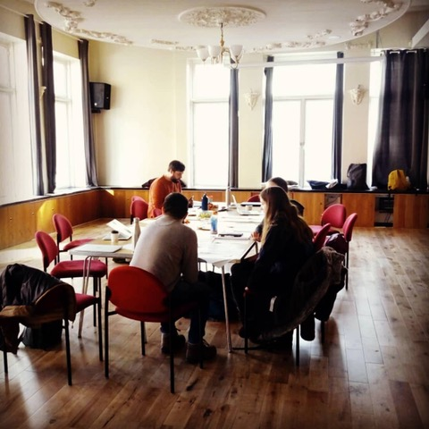 four people sat around table in big meeting room