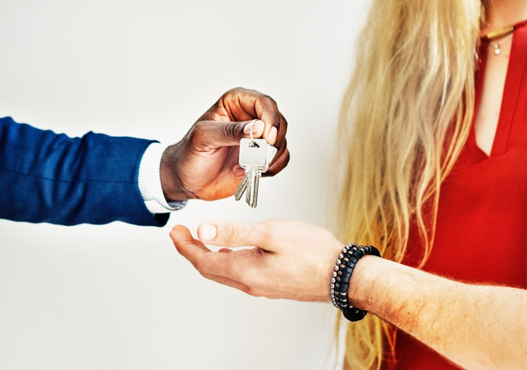 dealter handing car keys to woman in red dress