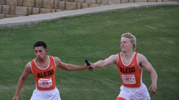 Regan Rice hands the baton to Gio Torez during the boys' 4x400 relay during friday's preliminaries at the regional meet.