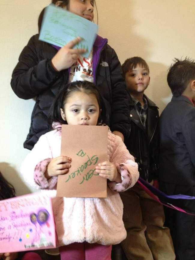 """One young girl holds a handmade card upside-down that reads. """"Dear Speaker B."""""""