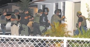 Officers prepare to enter a suspect grow house