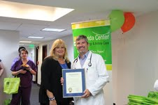 Maria Machado, Miami-Dade County Mayor's aide, and Dr. Frank J. Martell with the proclamation.