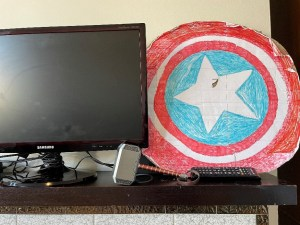 Homemade Captain America shield next to a television