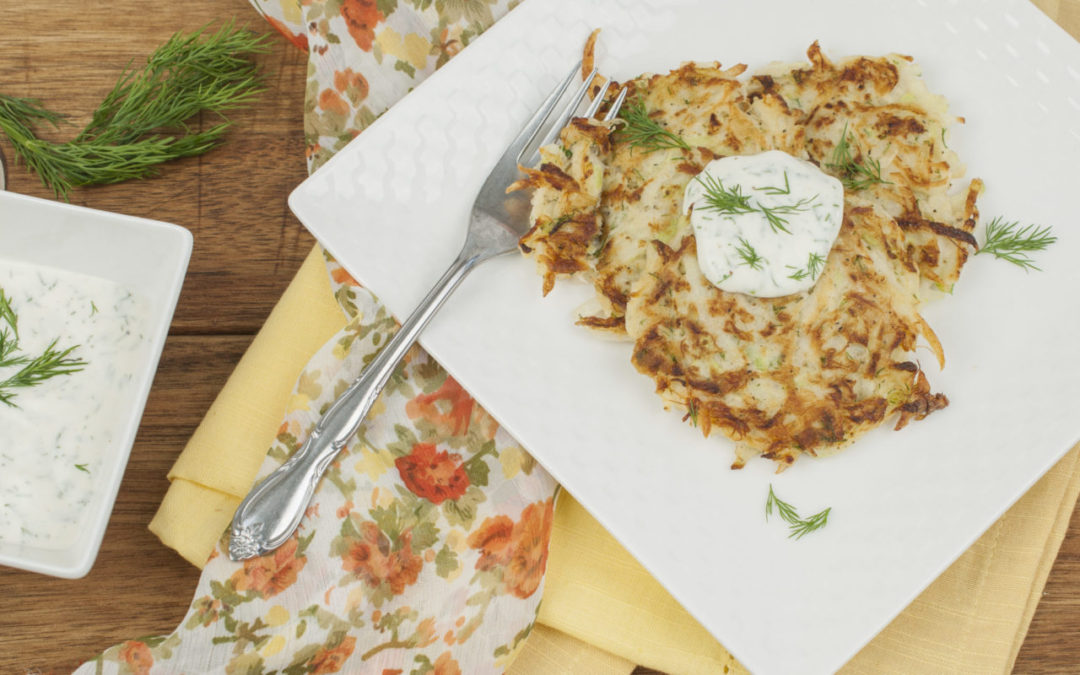 Golden panfried Kohlrabi Crab Cakes stacked upon a white plate with creamy dill sauce.