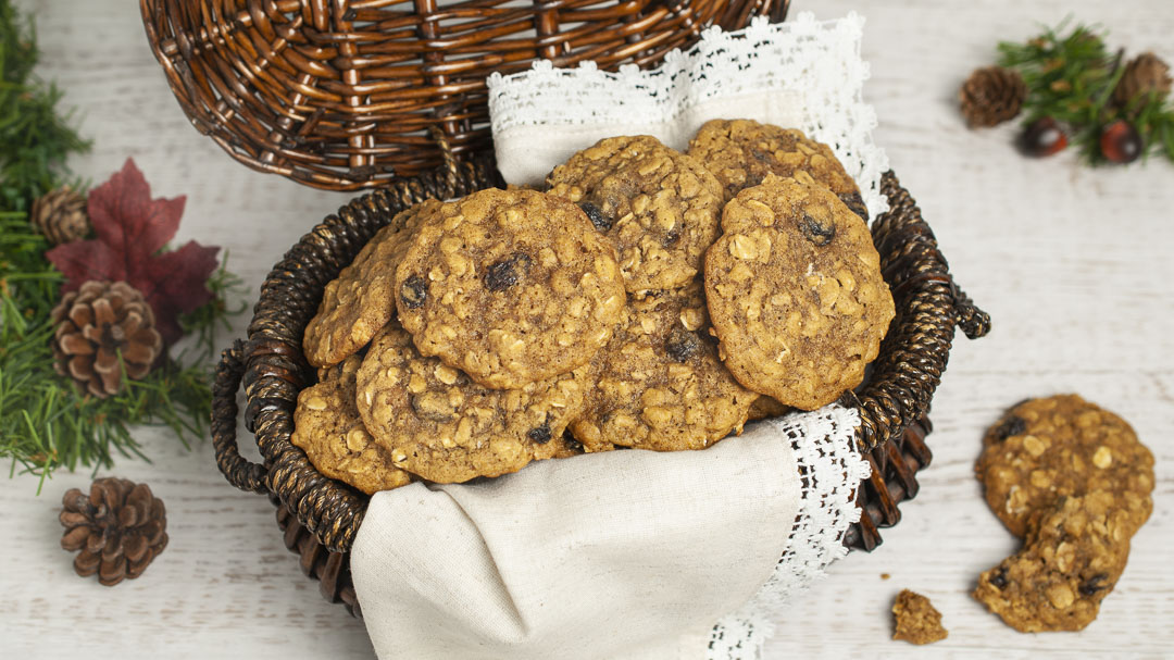 Baked Spicy Oatmeal Cookies piled high in a dark brown basket. The basket is lined with a lace napkin and rests on a light surface with pine cones and greenery to the side.