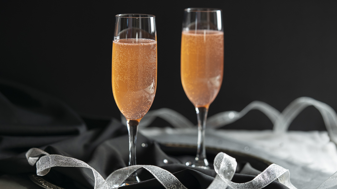 Two champagne glasses filled with Apricot Brandy Sparkler cocktail sit on a silver tray lined with black fabric, white ribbon and reflective crystal beads.