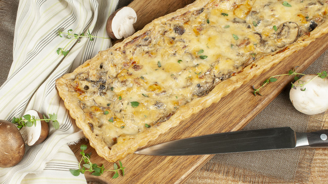 A baked Mushroom Gruyere Tart from Compelled to Cook sits, ready to be cut on a cutting board that is draped with a striped towel and scattered with mushrooms.