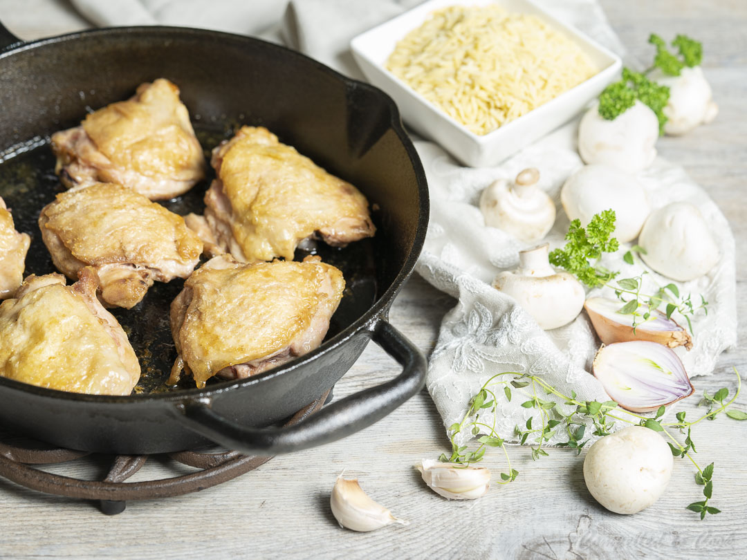 Panfried chicken thighs in a cast iron skillet in preparation for Skillet Chicken and Orzo.