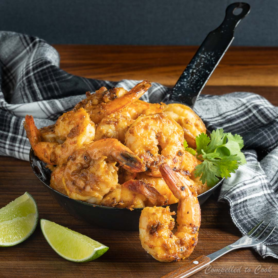 Spicy Miso Shrimp served in a small decorative skillet on a dark wooden board.