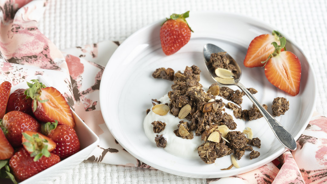 Ultimate Chocolate Almond Granola is scattered over yogurt and served with fresh strawberries in a shallow dish.