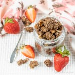 A jar piled high with Ultimate Chocolate Almond Granola and has strawberries scattered at its base.