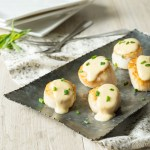 Scallops with Tarragon Cream Sauce arranged on a metal platter that sits on a table napkin.