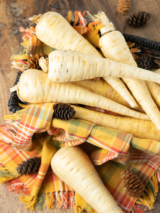 Raw parsnips stacked in a wicker basket lined with an orange checkered napkin and scattered with pinecones.
