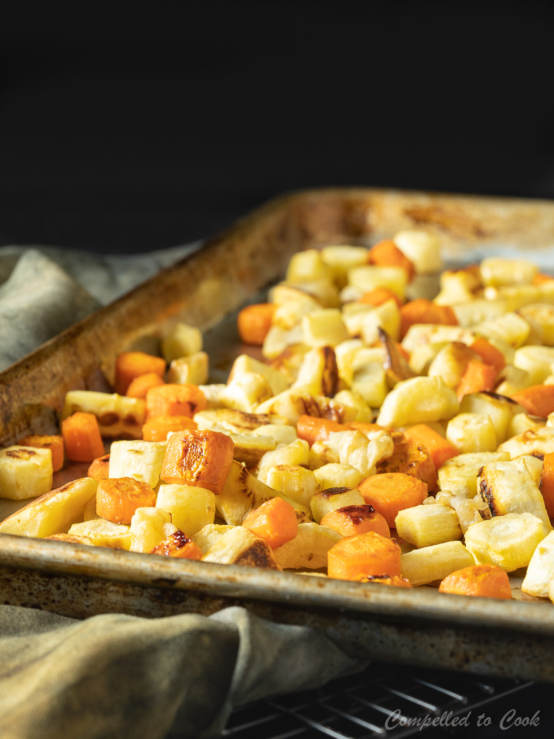 A sheet pan lined with roasted vegetable in preparation for Roasted Vegetable Soup.