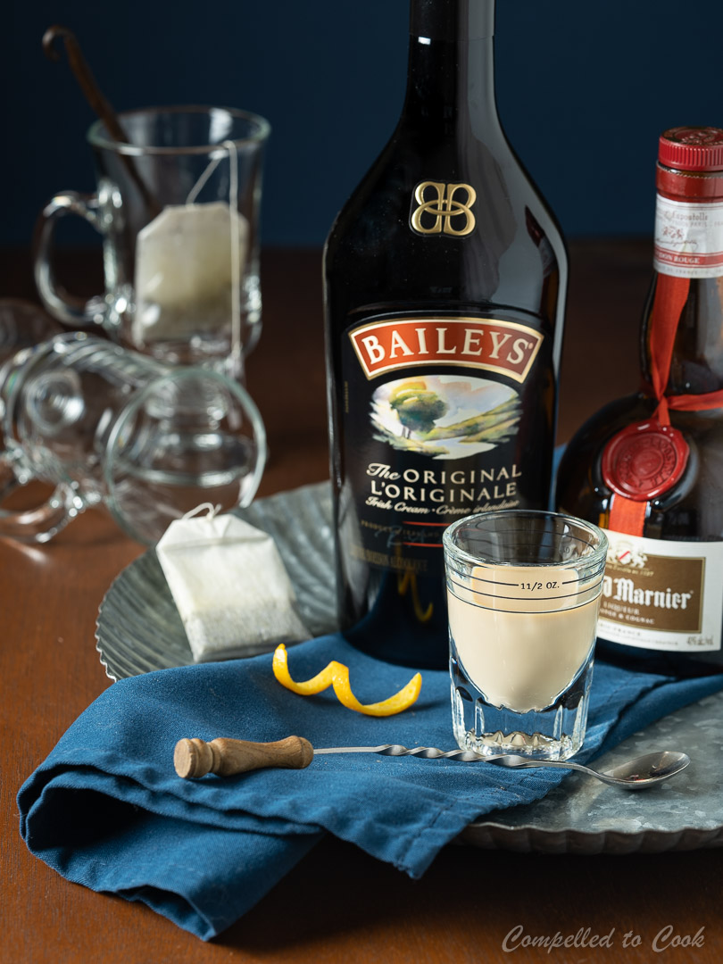 Ingredients for Baileys London Fog on a silver tray lined with a blue napkin.
