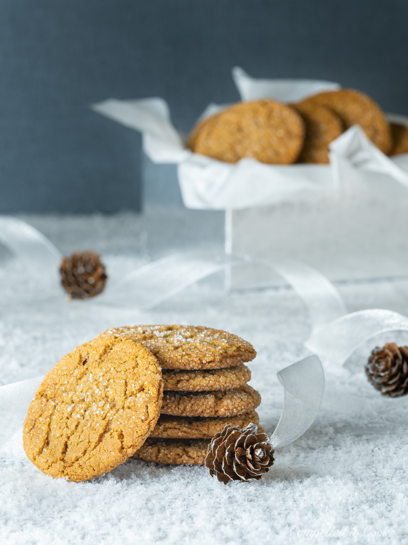 A stack of Molasses Crinkle Cookies that sit in front of a silver box filled with cookies and decorated with white ribbon and acorns.