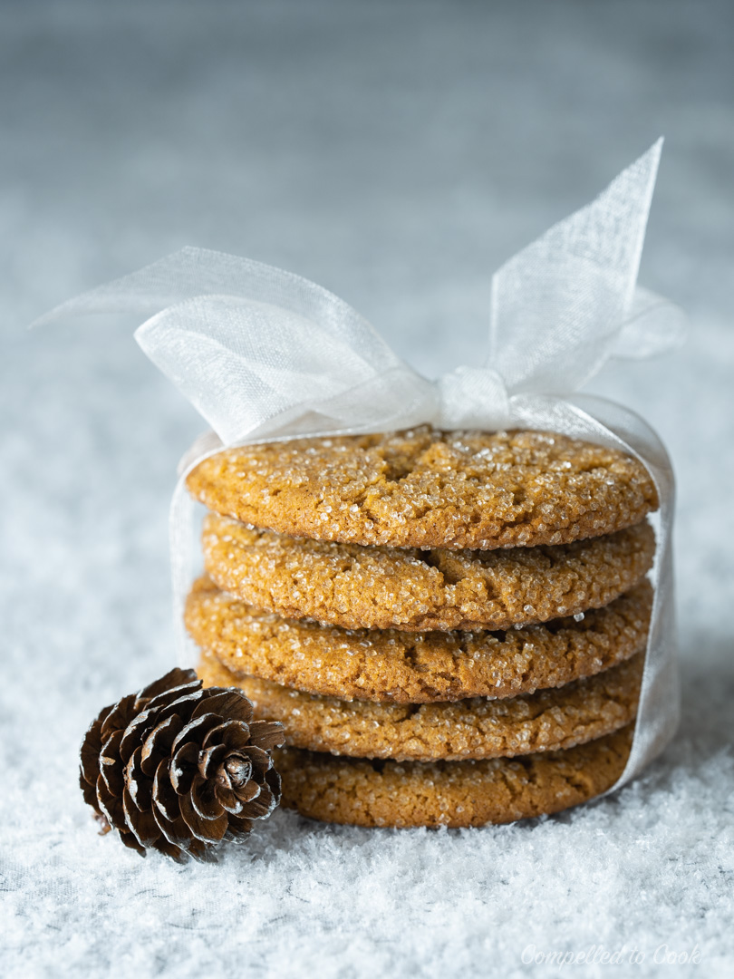 Molasses Crinkle Cookies stacked five high and tied with a white ribbon and decorated with an acorn.