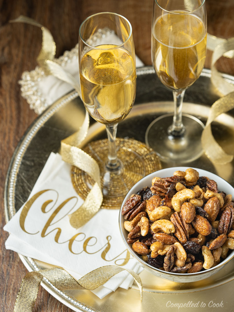 Five Spiced Mixed Nuts in a small bowl on a gold tray with white napkins and glasses of champagne.