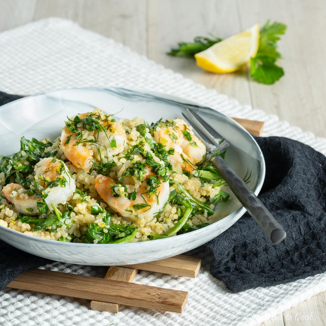 Herbed Quinoa Shrimp Bowls served in a shallow bowl resting on a black kitchen towel and wooden trivet.