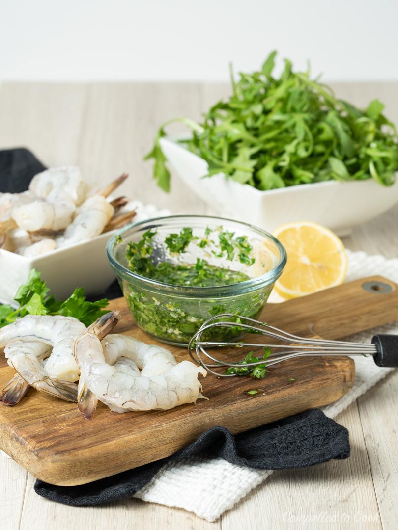Raw shrimp, arugula and lemon dressing in preparation for Herbed Quinoa Shrimp Bowls.