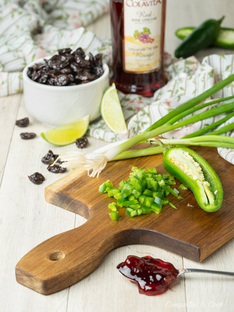 Ingredients for Cherry Salsa arranged on and around a wooden cutting board with a bowl of dried cherries in the background.