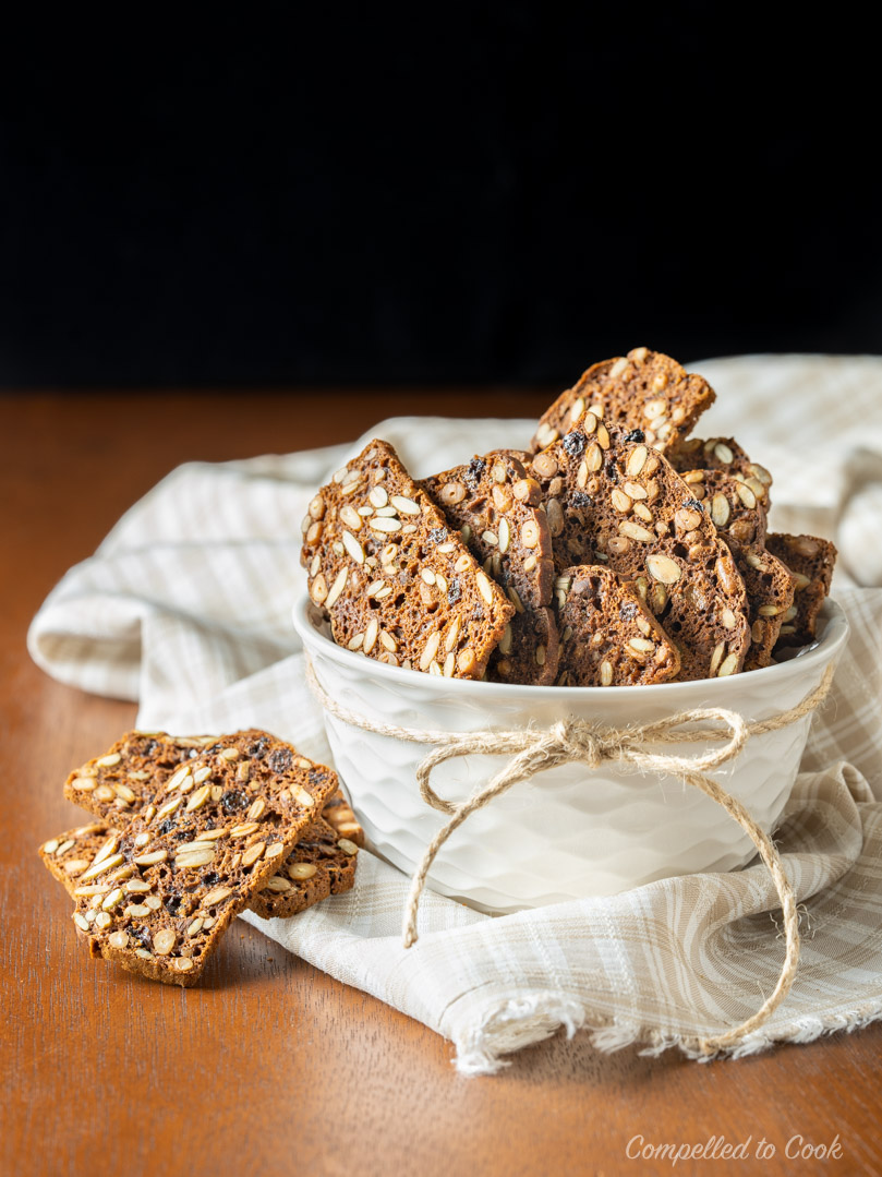 A white bowl piled high with Pumpernickel Seed and Nut Crisps.