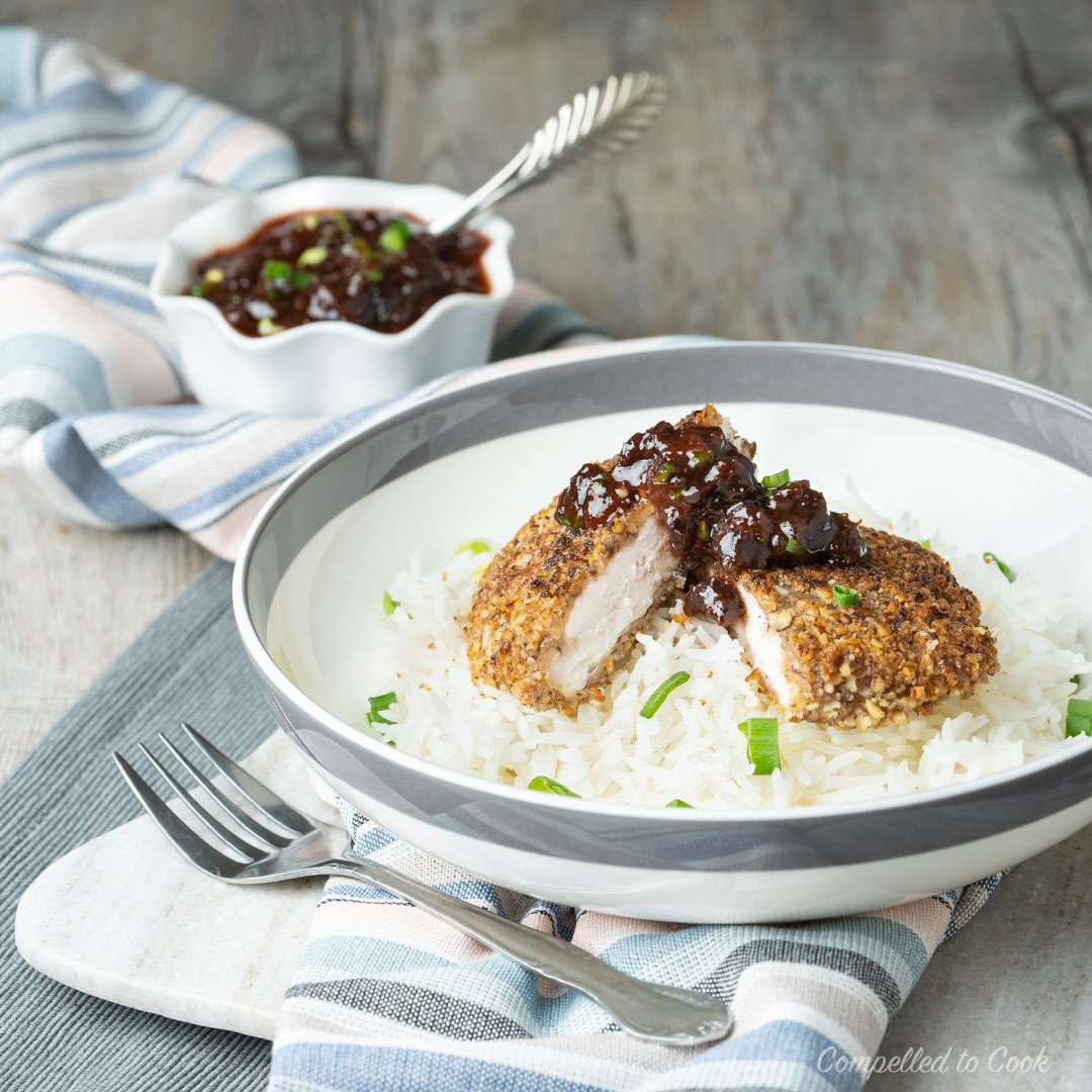 Pecan Crusted Chicken Cutlets served in a shallow bowl on top of rice with Cherry Salsa and green onions.