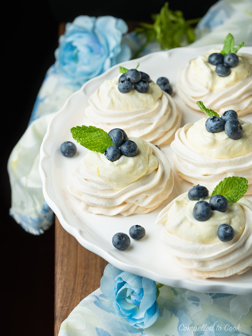 Lemon Cream Mini Pavlovas garnished with blueberries and mint sit on a white cake tray decorated with blue flowers.