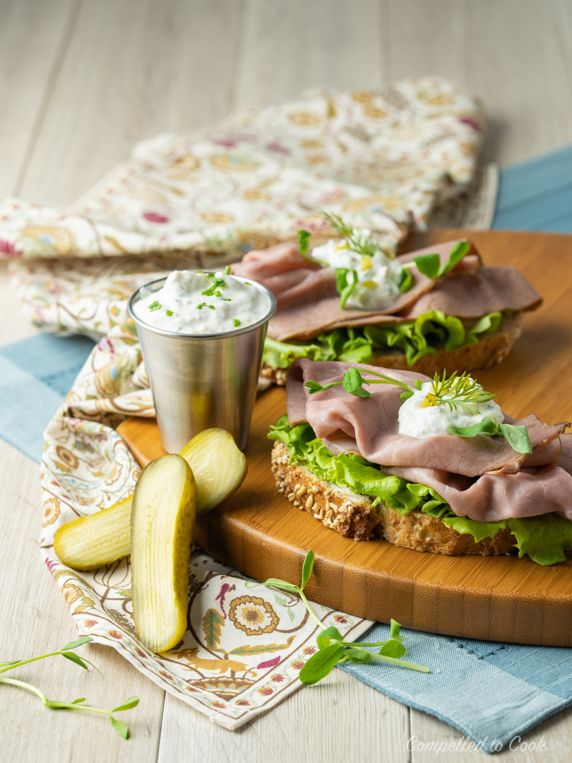 Horseradish Cream in a small silver cup served along side a roast beef sandwich served on a wooden tray.