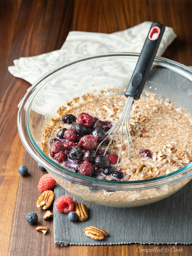 Ingredients for Baked Berry and Coconut Oatmeal in a large glass bowl ready to be whisked together.