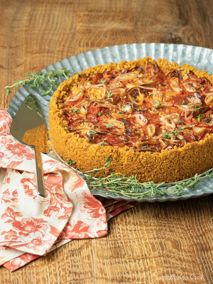 Tomato and Roasted Garlic Pie served whole on a scalloped silver platter, garnished with fresh thyme.