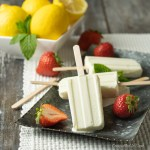 Creamy Lemon Pops stacked on a metal serving tray garnished with fresh strawberries and a bowl of lemons in the background.