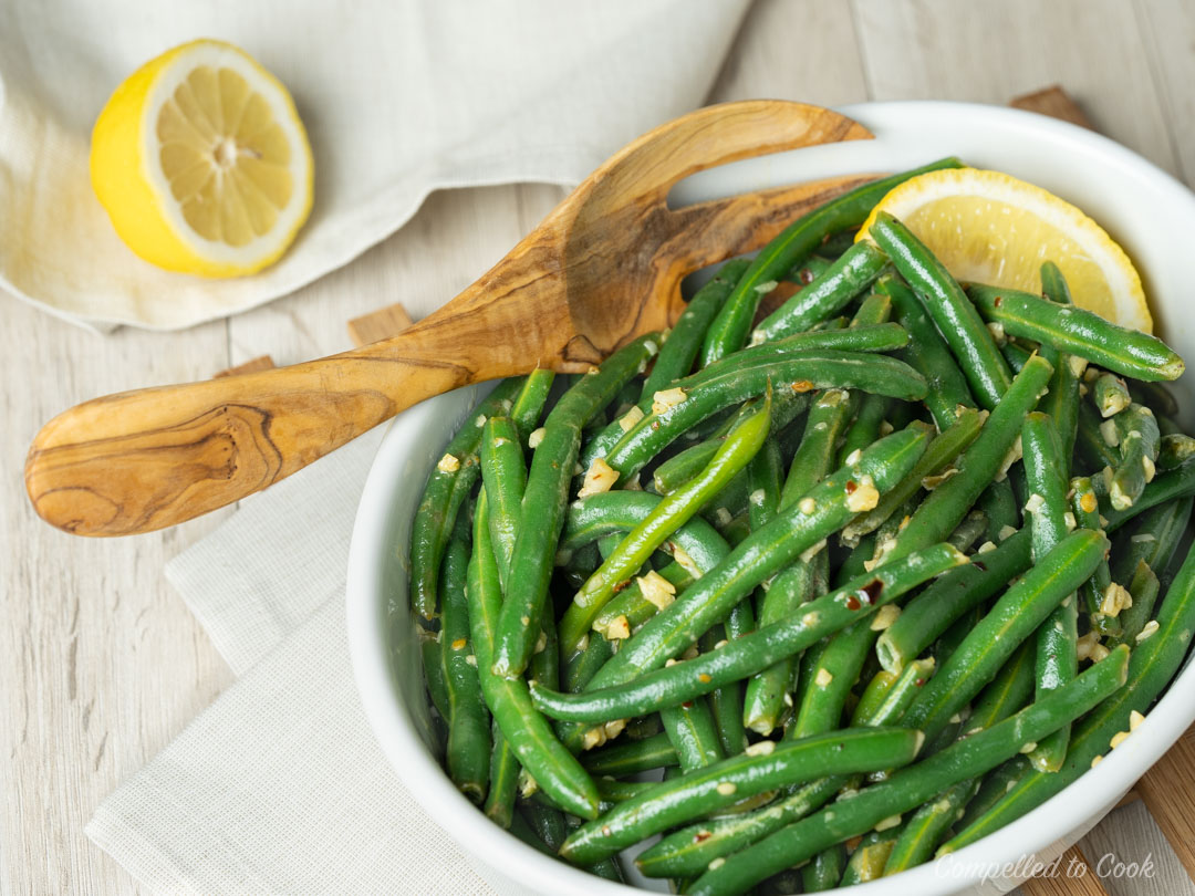 Garlicky Buttered Beans served in a shallow, oval dish with a wedge of lemon.