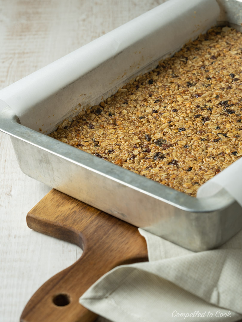 Nut Butter Granola Bars pressed into a 9x13 pan and ready for baking.