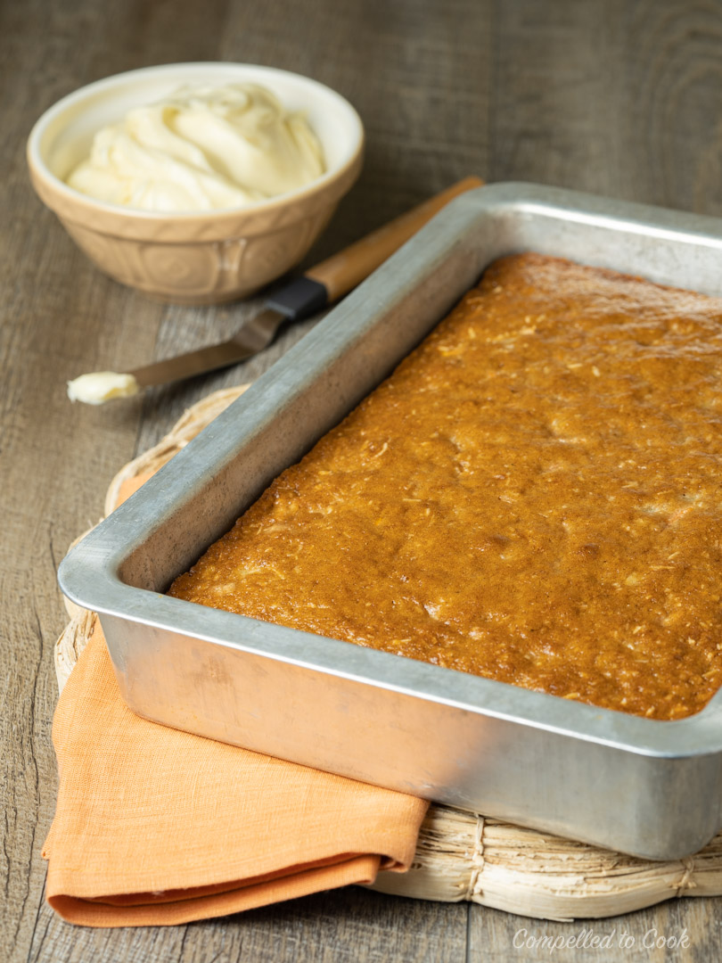 Super Moist Carrot Cake just out of the oven in a silver baking pan and icing in the background.