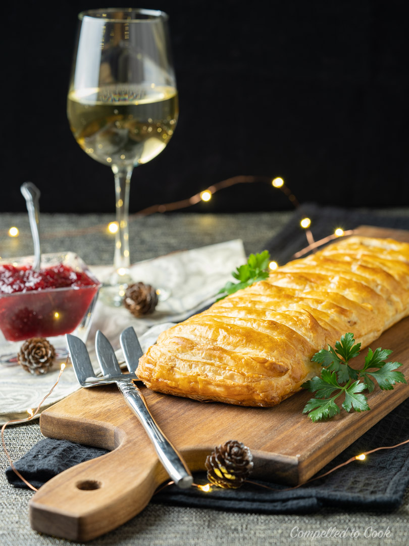 A golden baked Turkey & Chestnut Pastry Slice served whole on a wooden board garnished with fresh parsley.