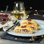 Slices of Turkey & Chestnut Pastry Slice arranged on a grey plate with cranberry sauce and fresh thyme.
