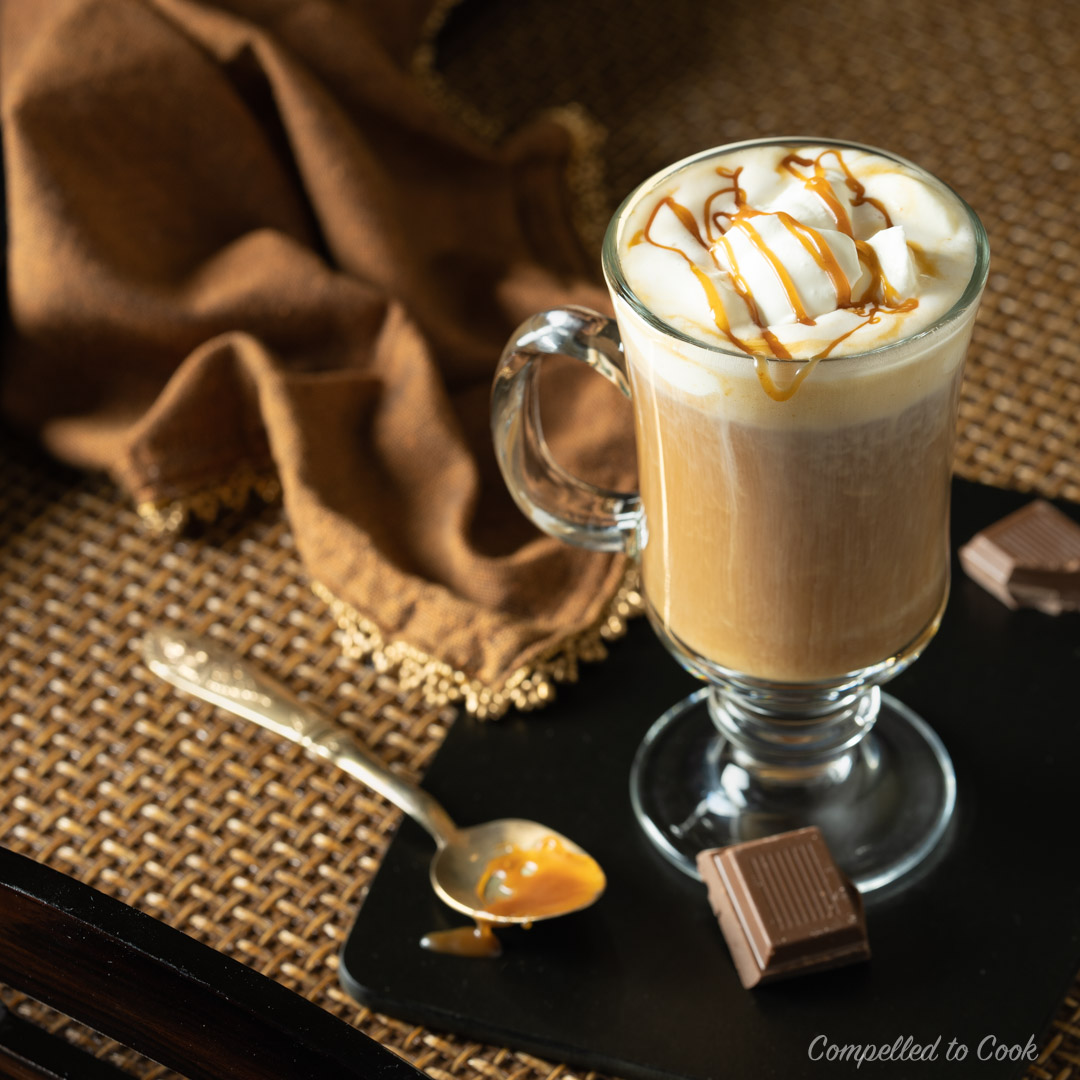 Caramel Irish Coffee drizzled with caramel sauce and served in a clear mug.