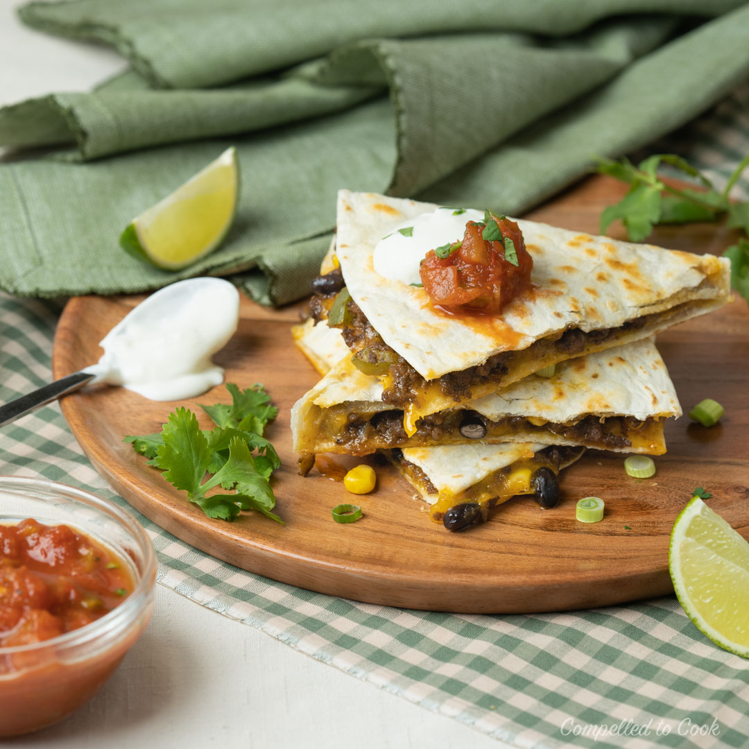 Beef and Black Bean Quesadillas cut and stacked three high on a wooden plate, garnished with cilantro and lime.
